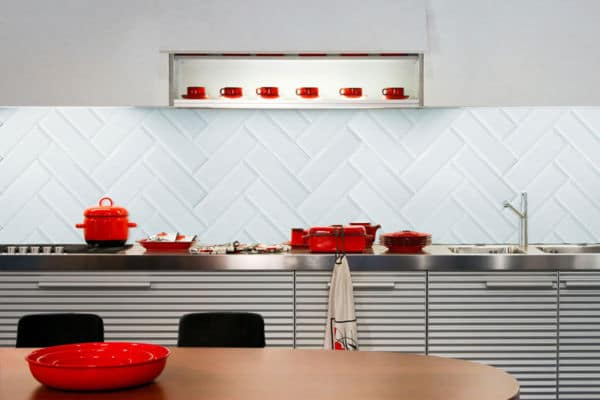 How to tile a kitchen splashback wall - A light blue kitchen splashback wall with distinct red pots and pans