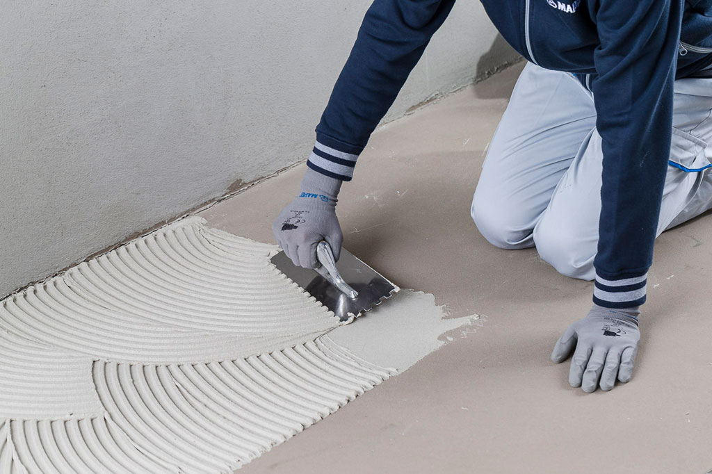 troweling white adhesive onto a floor